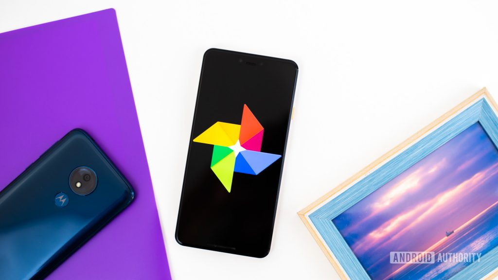 Google Photos logo on smartphone next to imaging accessories stock photo 1