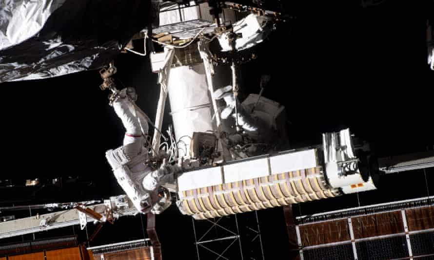 Thomas Pesquet de la ESA (izquierda) está conectado a un estabilizador de pie articulado portátil en el extremo del brazo robótico Canadarm2 que transporta paneles solares desarrollados hacia la estructura de celosía P-6 de la Estación Espacial Internacional, junto al astronauta estadounidense Shane Kimbrough.